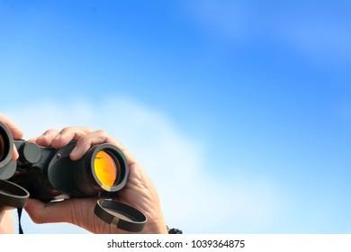 hand holding binoculars on blue sky background