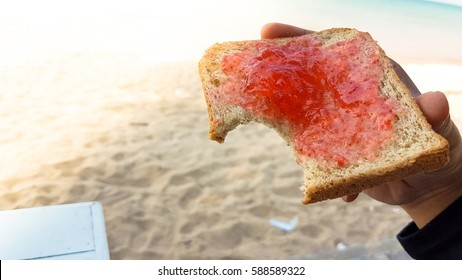 hand holding a bite toast with strawberry yam beside the sand beach with sunflare