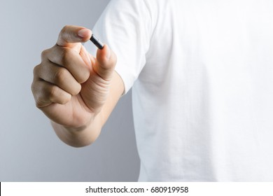 Hand holding black carbon charcoal capsule medicine pill or poison drug on white background