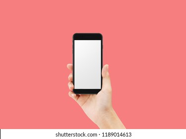 Hand holding black color mobile phone isolated on red background with empty space