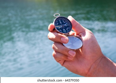 Hand holding the black compass