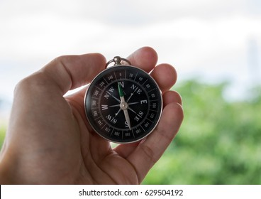 Hand holding Black dipping navigation compass pointing north outdoors