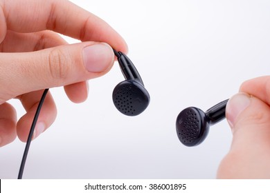 Hand holding a black earphone on a white background