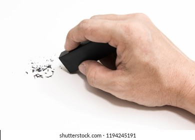 Hand holding black eraser scrap on paper background.  Error Eraser dust on white background. top view.