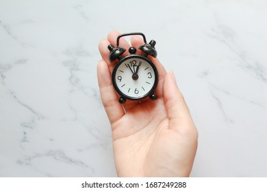 Hand holding Black larm clock on white marble background.
