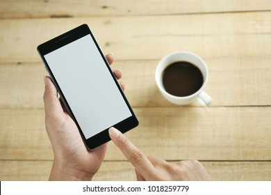 Hand holding black mobile smart phone with blank screen over wood table. technology and lifestyle concept.