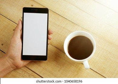 Hand holding black mobile smart phone with blank  screen with coffee cup on wood table . technology and lifestyle concept.