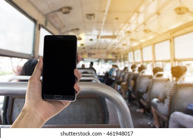 hand holding black mobile smart phone on Left side. Blurred inside bus with sunlight on the background.