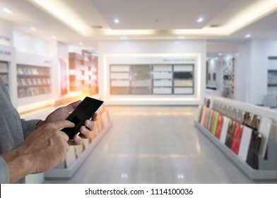 hand holding black phone with Modern Ceramic tiles Display in the Luxury Shopping Mall. Bussiness man pointing finger on screen smartphone on home material shop background