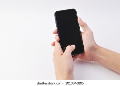 hand holding the black smartphone with blank screen on white background