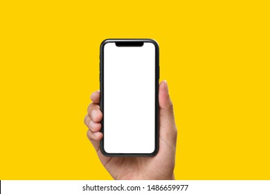 Hand holding the black smartphone with blank screen on yellow colour background