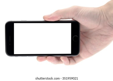 Hand holding the black smartphone with blank screen, isolated on white background.