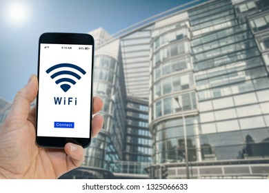 Hand holding a black smartphone with button connect to wireless internet hotspot on screen - Wifi hotspot in business place