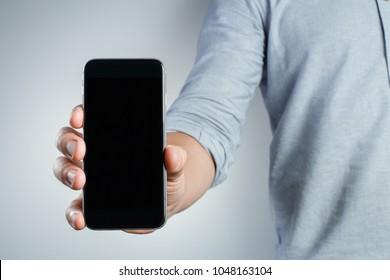 Hand holding black smartphone on white background