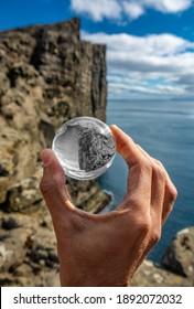 Hand holding black and white crystal ball with colorful view of high cliffs and black and white surroundings