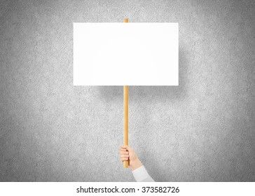 Hand holding blank banner mock up on wood stick. Empty board plank hold in hands.