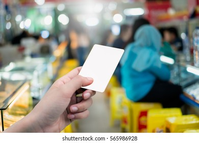 Hand holding blank credit card or ticket  at mall