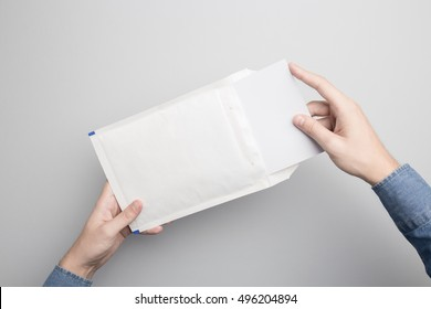Hand holding Blank padded Envelope Mock-up, ready to replace your design.