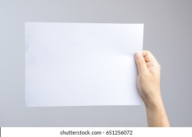 Hand holding blank paper easy replace with poster or brochure on white background