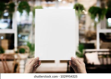 Hånd holder blankt papir plakat design for meny på restaurant, Mock opp plass for visning av meny eller design.