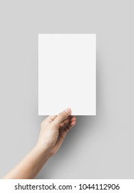 Hand holding blank paper sheet A5 size on grey background.