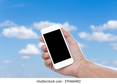 Hand holding blank screen mobile phone with blue sky background