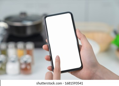 Hand holding blank screen of smartphone at home in kitchen. for graphic display montage.