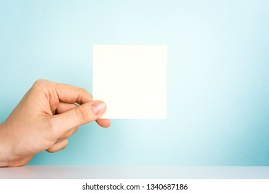 Hand holding a blank sticky note for text with over desk on blue background. Office message concept.