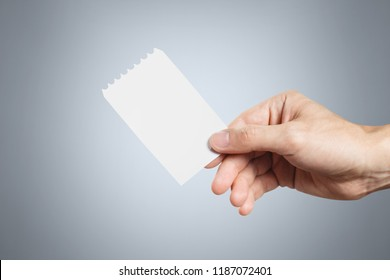 Hand holding a blank ticket on grey background