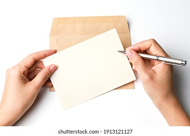 Hand holding blank white card and pen with paper envelope template mock up. Greeting card or invitation mailing concept.