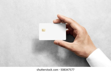 Hand holding blank white credit card mockup with rounded corners. Plain creditcard mock up template with electronic chip holding arm. Plastic bank-card display front design. Business branding.