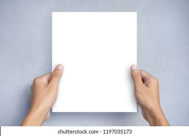 Hand holding a blank white paper sheet mock up on a gray background. Blank Brochure Template, Leaflet