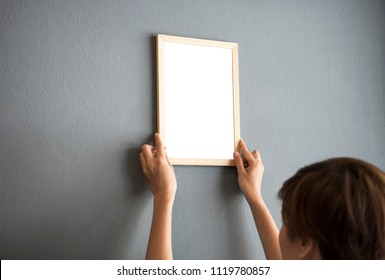 Hand Holding Blank white Photo Frame Hanging Wall for Design Mockup Template.