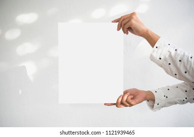 Hand Holding Blank white Photo Frame with Sunlight for Design Mockup Template.