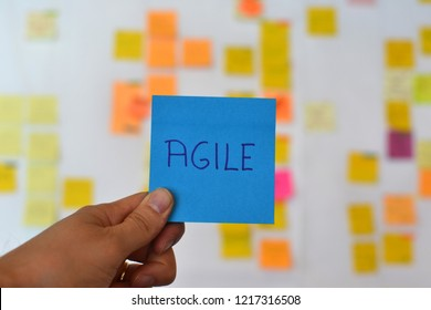 A hand is holding a blue agile sticker and there is a Kanban board of agile methodology on the background, which is a developing trend in Information Technology (IT) business.