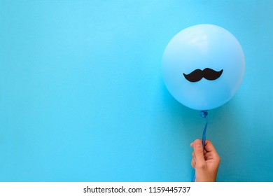 Hand holding blue balloon with a paper mustache on blue paper background. Cut out style. Father's day or mustache day concept