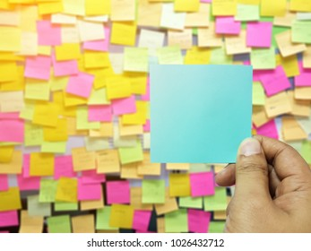 hand holding blue empty notepaper with background of colorful notes on board.