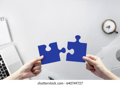 Hand holding blue paper cut jigsaw puzzle on white office desk table top view with copy space for teamwork concept