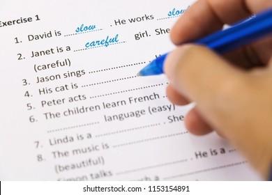 Hand, die einen blauen Stift hält, Prüfung auf Englisch