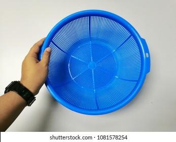 Hand holding blue plastic basket on white background