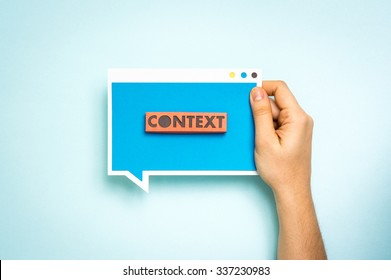 """Hand holding blue speech bubble with the text """"context"""". """"Context Marketing"""" concept."""