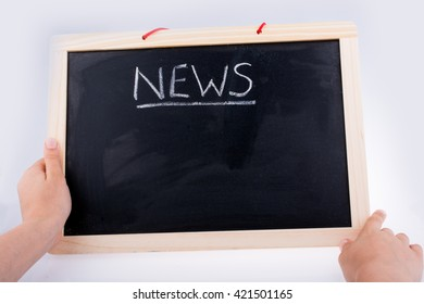 Hand holding the board  with the title of news