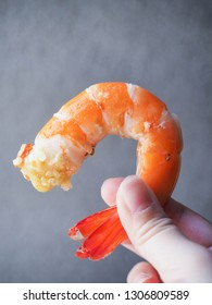 Hand holding boiled shrimp that already dip in sauce.