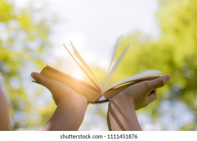 hand holding book on sky in park, knowledge and wisdom concept