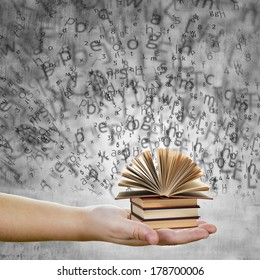 A hand holding books with words and letters representing education and knowledge concept