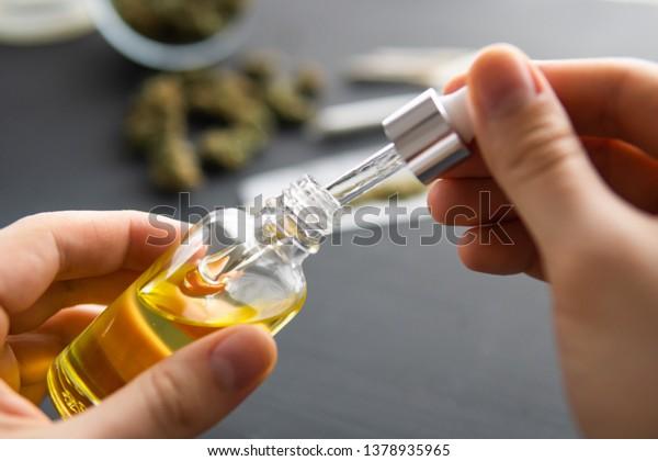 Handhalten Flasche Cannabis Öl in Pipette, natürliche Kräuter, medizinisches Marihuana Konzept, CBD Cannabis OIL. Hanfprodukt, Nahaufnahme,