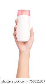 Hand holding bottle lotion isolated on white background