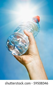 A hand holding a bottle of mineral water into the sun on a blue sky background - intentional flare.