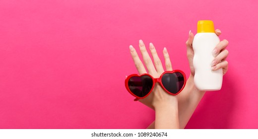 Hand holding a bottle of sunblock and sunglasses