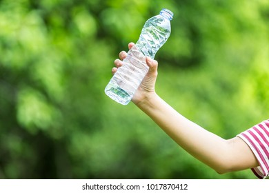 Hand holding a bottle of water in a natural background.